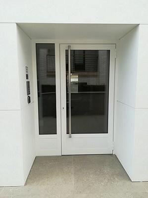 puerta de aluminio de entrada en color blanca y vidrio oscuro