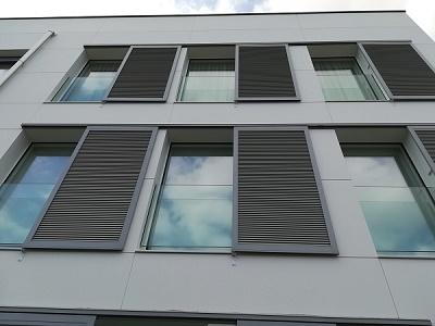 fachada de vivienda con contraventana corredera gris y barandilla de vidrio