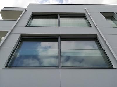 fachada de vivienda con ventana de aluminio corredera hoja oculta, persiana graduable  y barandilla de vidrio