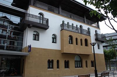 fachada de piedra con ventanas de aluminio en color marron con curvas y rectas