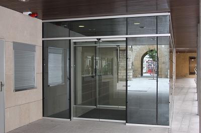 puerta corredera automática de 2 hojas acristalada, integrada en muro de cortina