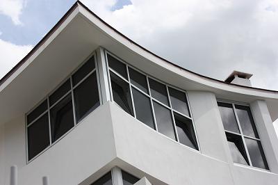 fachada blanca de vivienda con ventanas de aluminio en plata y vidrios oscuros